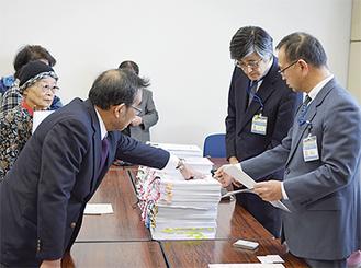 市長宛ての陳情書と署名を坂和伸賢建築局長(手前右)に手渡す山仲代表(同左)