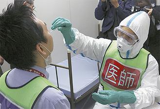 防護服を着用して患者と接する医師(右)