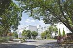 正門を入り、ゆるやかなスロープを上ると、緑の木々と白く明るい南高校の校舎が見える(2014年9月12日撮影)