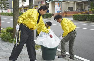 道路の端や茂みからごみを拾い集めるメンバー