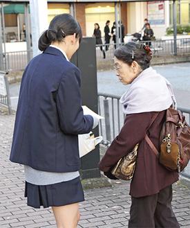 通行人にチラシを渡す中学生