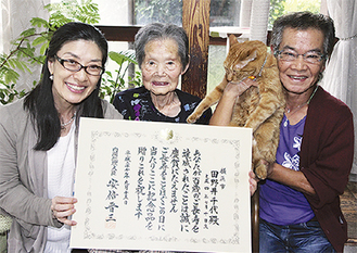 お祝いを喜ぶ田野井千代さん(中央)と藤雄さん、猫のたまちゃん