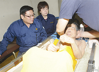 ▲地元の議員らが見守る中、2人から入浴の補助を受ける被災した高齢者           (提供写真)