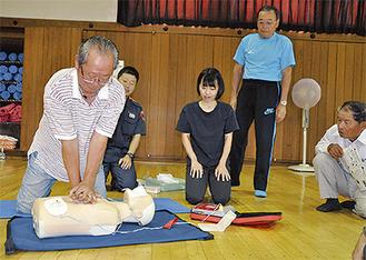 消防署職員から手ほどきを受け、AEDを使用ながら心肺蘇生法に挑戦する参加者