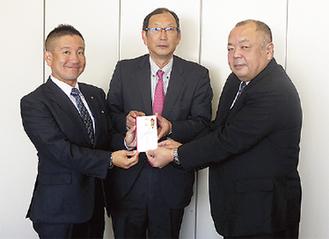 寄付を手渡す根本社長(左)と長谷川会長(中央)