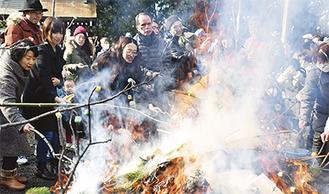 焚き上げの炎で色とりどりの餅を焼く参加者