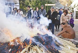勢いよく燃える炎の周りで暖を取る参列者たち