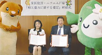 協定書を手にする小山内区長(左)と福原代表