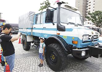 災害対策活動車のウニモグの前で写真撮影を楽しむ親子