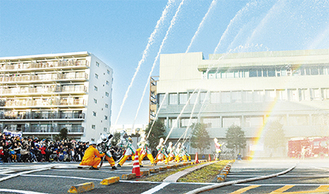 多くの来場者が見守る中、区役所の建物に向かって行われた一斉放水
