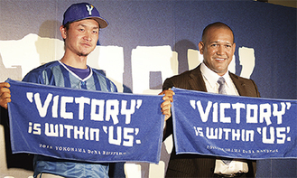 新スローガンが書かれたタオルを手にするラミレス監督(右)と大和選手