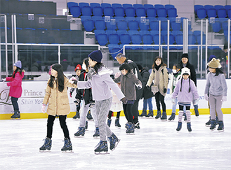 手を取り合ってアイススケートを楽しむ参加者