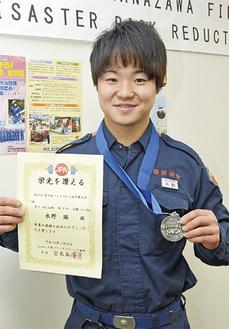 メダルと賞状を手にする水野さん