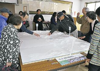 小学生が作成した地形模型に関心を寄せる住民ら
