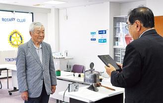江上会長から表彰される本間さん(左)