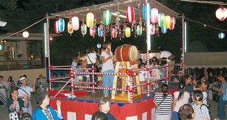 祭りやぐらにのぼり踊る子どもたち