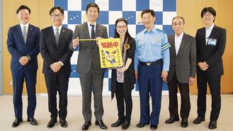 横断幕を手にする秋葉社長と齊藤区長(中央)、関係者ら