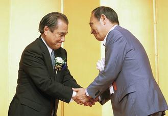 力強く握手を交わす桐生議長(左)と菅官房長官