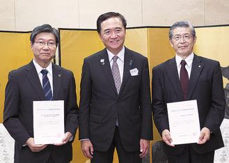 黒岩知事から手渡された選定書を持つ山下純正総長(右)と野田政樹院長(左)