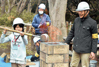 窯に砂鉄を入れる参加者