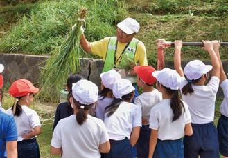 草いかだの説明をするボランティアの川越勝雄さん