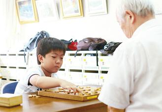 指導者の今野さん(右)と将棋を指す佐々木君