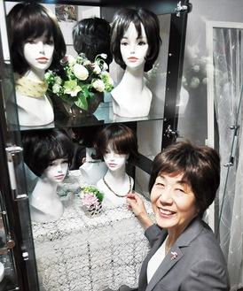 自社商品を前に微笑む武田さん。「自信が持てるものを」と呼び掛ける
