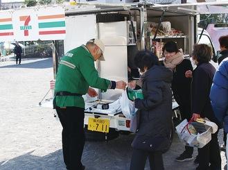 移動販売車で買い物をする住民ら