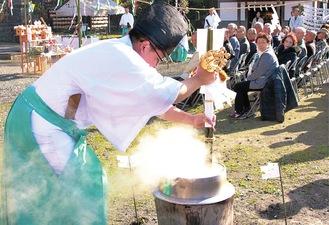 煮立った湯をかき混ぜる神職