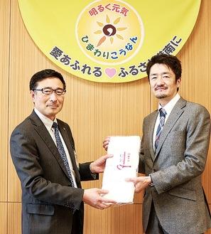 マスクを寄付する倉田代表取締役(右)と今冨区長(左)