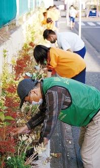 苗植えに取り組む同会メンバーと同校の生徒たち