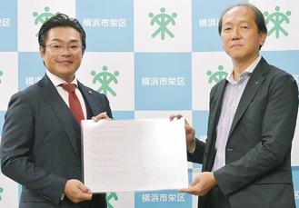 (株)三春情報センターの春木代表取締役(左)と協定書を交わす冨士田栄区長