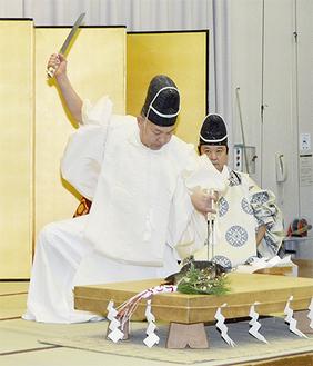 烏帽子、直垂をまとい、伝統作法で鯉をさばく調理師