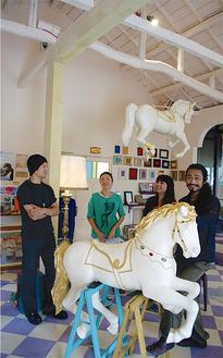 築70年の米軍ハウスをリノベーションしたスタジオで寺道さん(右)とスタッフ。メリーゴーランドの馬は自然素材にこだわり、本体の屋根や柱にはライトアップも施してあり移動式とはいえ本格的だ