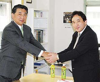 上野会長(左)と握手を交わす大石専務理事