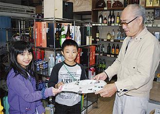 協賛店に紙面を手渡す児童