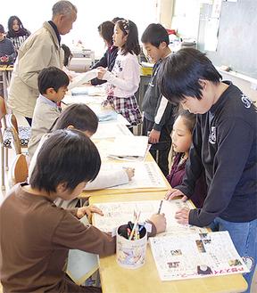 4年2組の児童(右列)から新聞づくりを聞く来場者