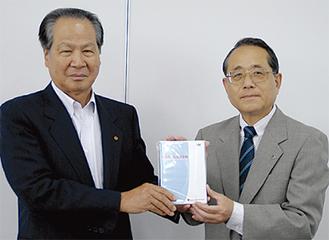 DVDを手渡す日赤の近藤事務局長(右)と教習所協会の福澤会長