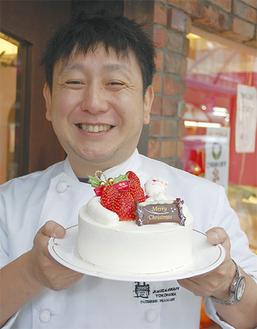 ケーキを手にする古屋さん