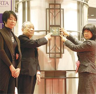 式典で最後の作品を取り付ける小谷社長(中央)ら