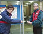印刷物を受け取る栗田会長(右)