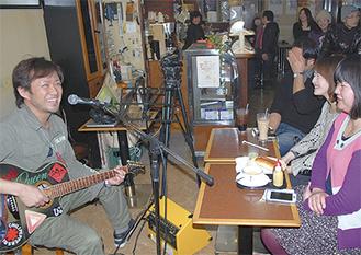 野毛の「カフェ・カルディー」で歌うヒューマンロストの鈴木磨さん(写真左)