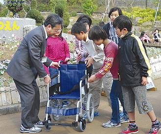 車椅子を受け取る市川園長(写真左)