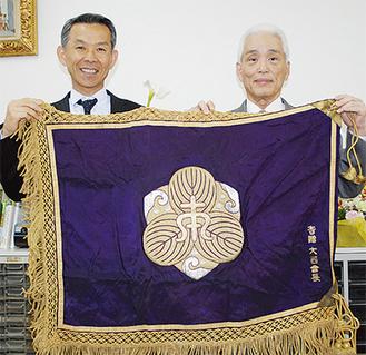 校旗を手に田中校長(左)と庄司さん