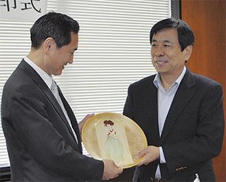 記念品を贈り合った金庁長(右)と牧野中区長(当時)