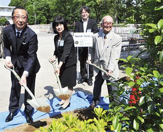 土入れする山本会長(写真左)