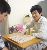 将棋部の仲間と指す渡辺さん(右)