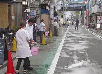 店舗前で水を撒く(写真は昨年)