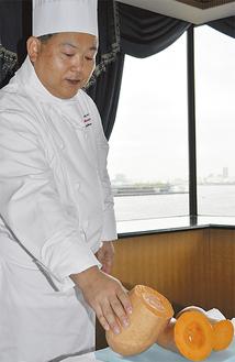 オレンジズッキーニを手にするシェフ・パティシエの松尾さん