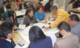 地図に課題を書き込み、街の将来を議論する参加者ら